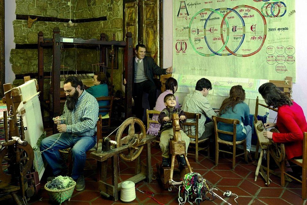 Domenico Caruso (a sin.) seduto al telaio in uno degli ambienti della Scuola Tappeti di cui è titolare a San Giovanni in Fiore (Cs) - Ph. Scuola Tappeti Caruso