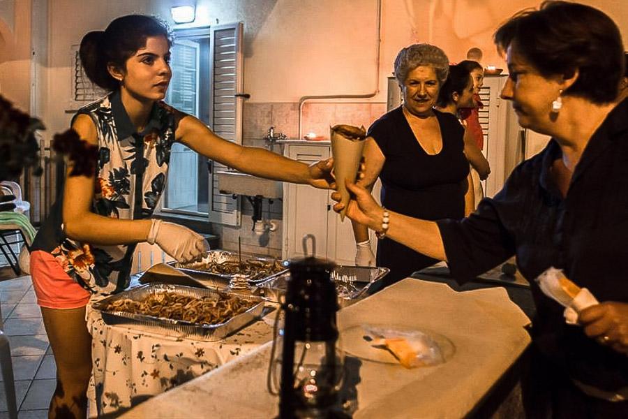 Una ragazza di Tricase Porto serve la frittura di pesce durante una delle cene 'on the road' - Ph. by Le Mamme del Borgo