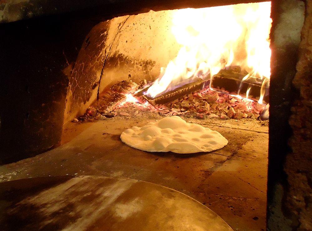 Cottura di una focaccia in un forno a legna