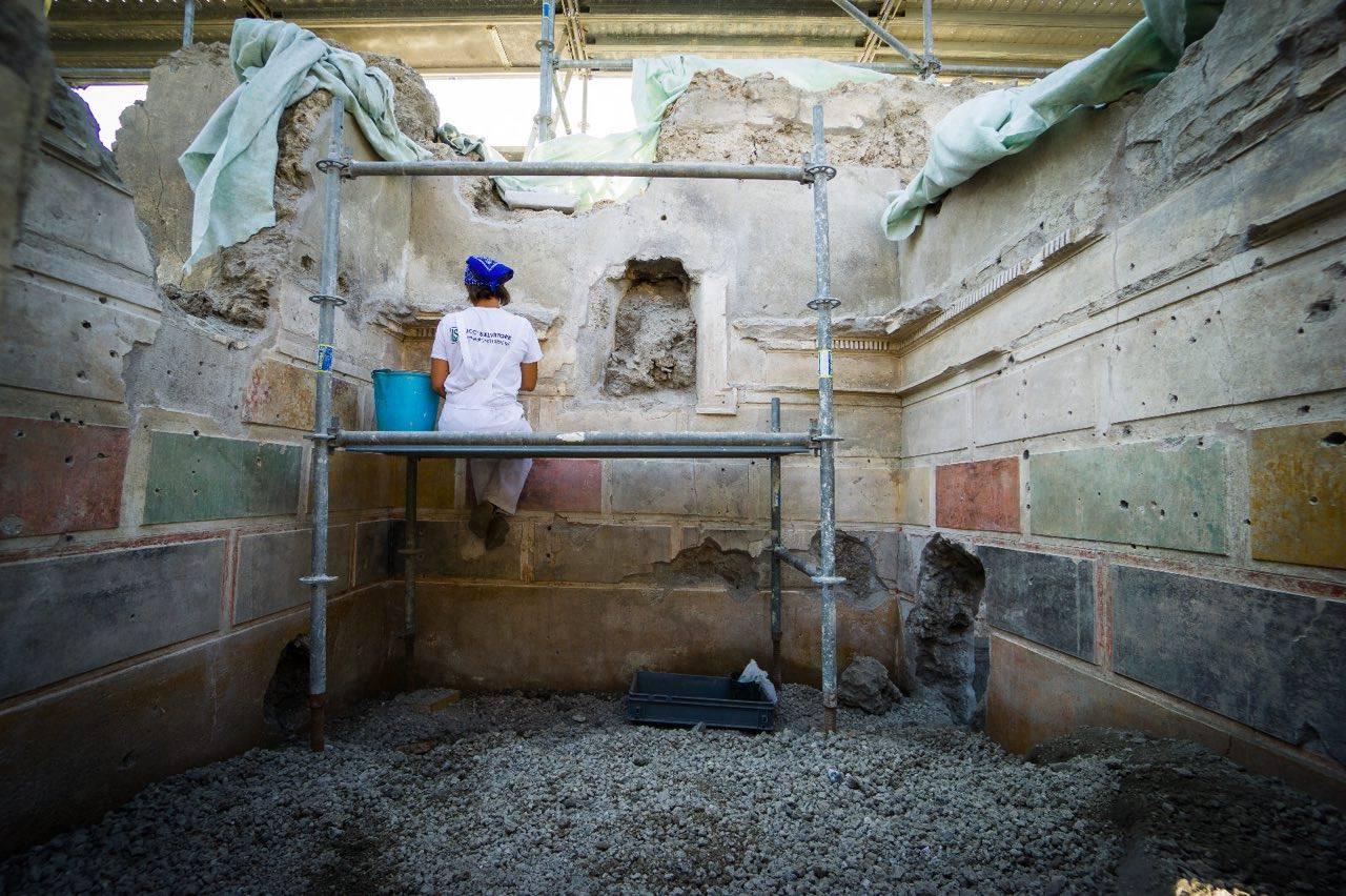 Restauratrice al lavoro sulle decorazioni in I° stile della Casa di Giove, II sec. a.C. - I sec. d.C., Pompei - Image by Parco Archeologico di Pompei' / Foto di Cesare Abbate