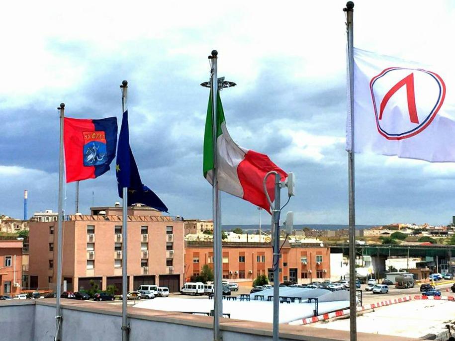 La bandiera spartana (a destra) sventola fra le bandiere del Porto di Taranto