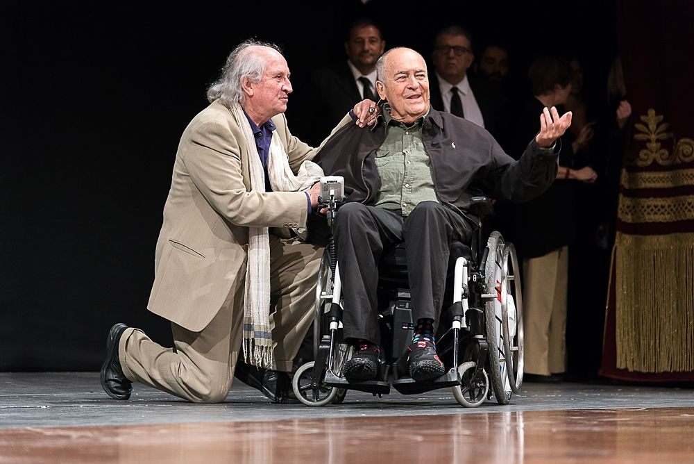 Vittorio Storaro saluta Bernardo Bertolucci (a destra) sul palco del Teatro Petruzzelli, Bif&st 2018 - Ph. – Ph. © Tiziana Rizzi