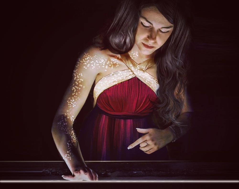 Erica Abelardo sand artist al lavoro sul piano luminoso