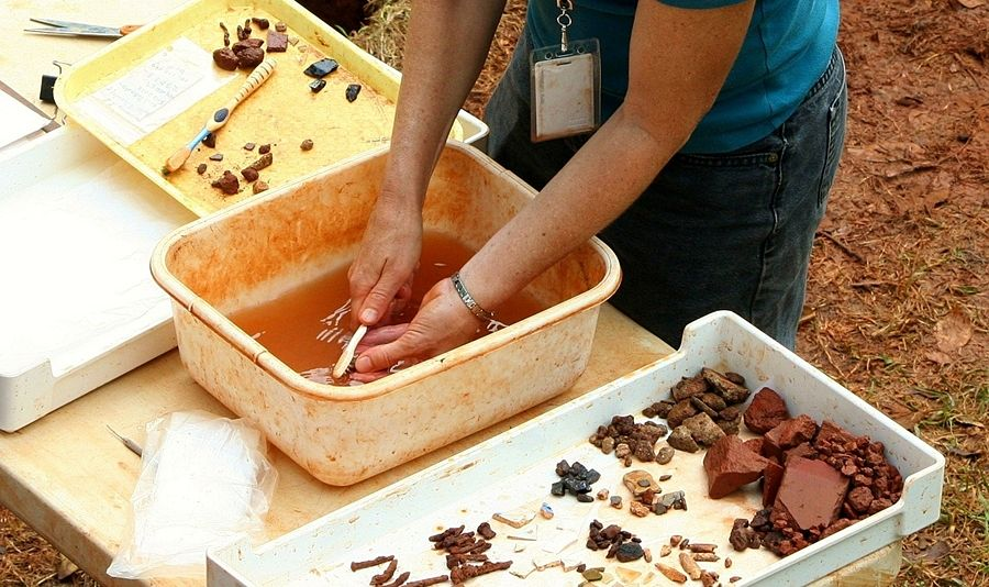 Pulizia dei reperti durante uno scavo archeologico - Ph. James DeMers   Public domain